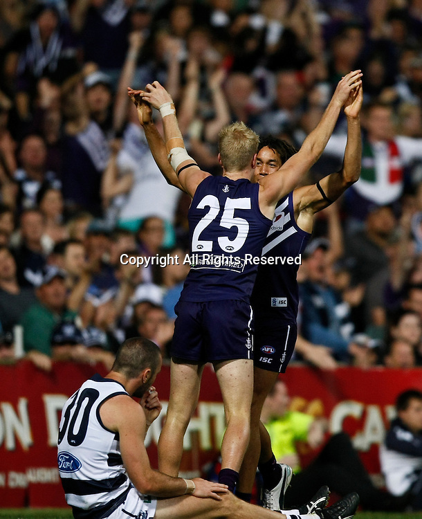 31.03.2012 Subiaco, Australia. Fremantle v Geelong. Tebdai Mzungu and Josh Mellington celebrate a goal while Geelong defender Matthew Scarlett looks on during the Round 1 game played at  Patersons Stadium.