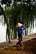 A Vietnamese man sweeps a sidewalks by early morning, Hoan Kiem Lake, Hanoi, Vietnam, Southeast Asia