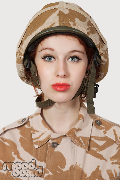 Portrait of young woman in military uniform against gray background