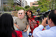 """04/25/12-  Andy DeLisle.Damian Charette, left, and Zarco Goercero, right, pose for cameras in masks Goercero created at Civic Space Park on Wednesday April, 25 2012 in Phoenix, AZ. Goercero poses as the devil and calls Brewer and Arpaio his """"servents""""."""