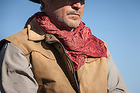 Red scarf on a cowboy with golden vest and striped shirt against blue sky. Model Released - Dean Spinelli.