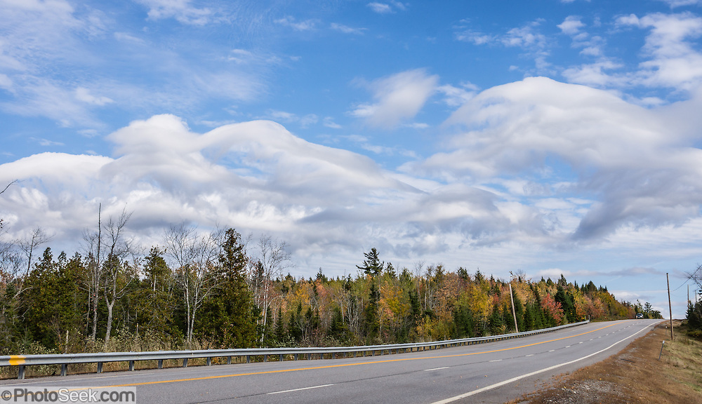 Arch-shaped clouds (some resembling jellyfish) blow over State Highway 9 in Maine, USA.