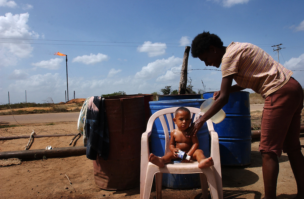 Siadlys Bajuelo washes her one year old son Manuel Alejandro Brito.  Up until a few months ago Bajuelo had to walk 2km to retrieve water to use at home.  She now gets water delivered to her home 3 times a week by a PDVSA truck.  Across the street from her home PDVSA is building a fresh water well that will supply running water directly to Bajuelo's home as well as other homes in the community.  PDVSA has increased their spending on social programs from 29 millions US$ in 2003 to 1.7 billion in 2004.  20% of their 50 billion dollar investment budget is being used for social development.  Critics claim that this is hurting PDVSA's ability to continue producing oil and that an oil company shouldn't be involved in social programs.  Proponents claim that this is a new PDVSA with a responsibility to help the impoverished communities in Venezuela.