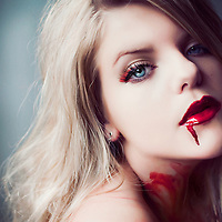 Close up of young woman with blonde hair and red blood on lips
