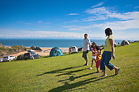Family (parents, son and daughter) playing at campsite<br /> Cars and tents overlooking beach<br /> Three Cliffs Bay Holiday Park<br /> Gower Peninsula<br /> County of Swansea<br /> South<br /> Camping and Caravanning<br /> Accommodation
