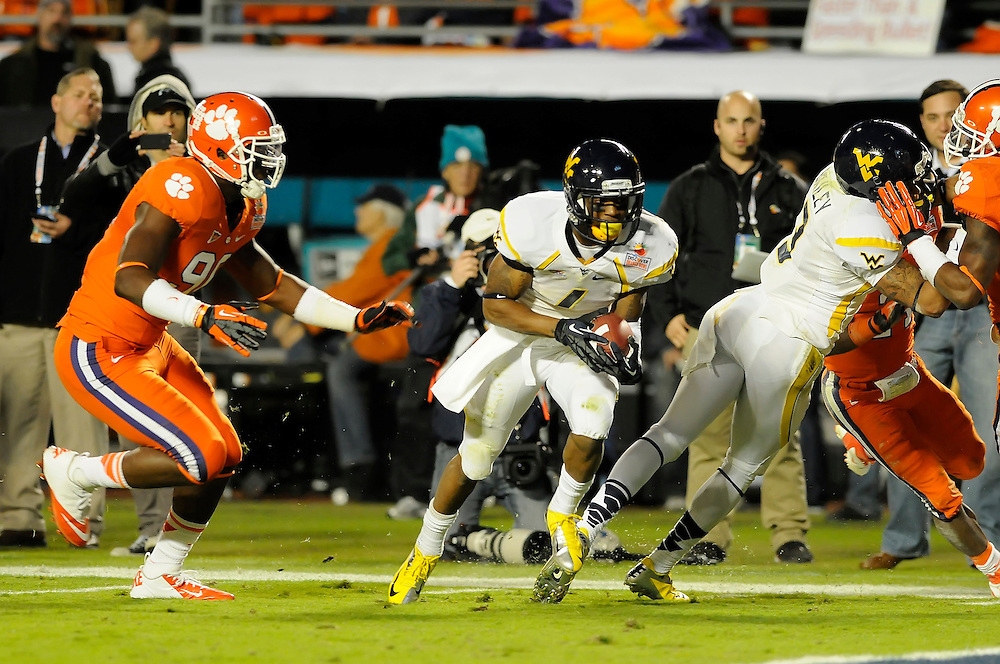 January 4, 2012: Tavon Austin #1 of West Virginia runs past Malliciah Goodman #97 of Clemson during the NCAA football game between the West Virginia Mountaineers and the Clemson Tigers at the 2012 Discover Orange Bowl at Sun Life Stadium in Miami Gardens, Florida.