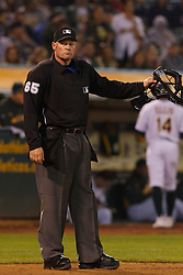 May 18, 2011; Oakland, CA, USA;  MLB umpire Ted Barrett (65) stands behind home plate after calling out Oakland Athletics second baseman Mark Ellis (back) on strikes against the Minnesota Twins during the ninth inning at Oakland-Alameda County Coliseum.  Minnesota defeated Oakland 4-3 in 10 innings.