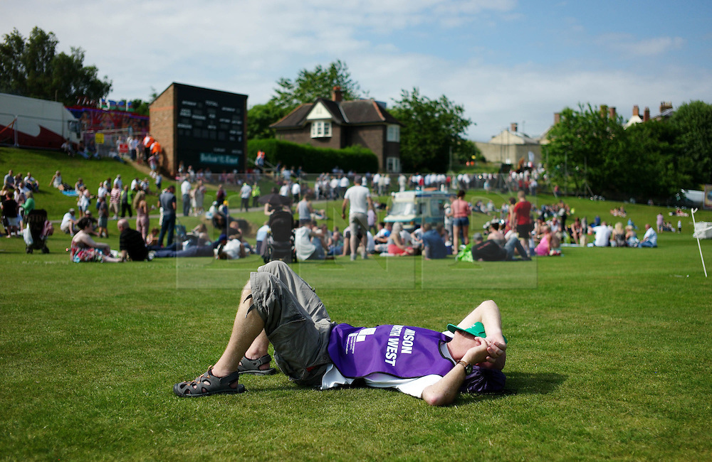 """© Licensed to London News Pictures. 13/07/2013<br /> <br /> Durham City, England, United Kingdom<br /> <br /> A man rests on the grass after marching to the Racecourse during the Durham Miners Gala.<br /> <br /> The Durham Miners' Gala is a large annual gathering held each year in the city of Durham. It is associated with the coal mining heritage of the Durham Coalfield, which stretched throughout the traditional County of Durham, and also gives voice to miners' trade unionism. <br /> <br /> Locally called """"The Big Meeting"""" or """"Durham Big Meeting"""" it consists of banners, each typically accompanied by a brass band, which are marched to the old Racecourse, where political speeches are delivered. In the afternoon a Miners' service is held in Durham Cathedral <br /> <br /> Photo credit : Ian Forsyth/LNP"""