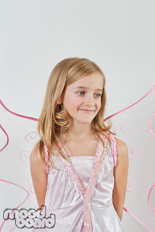 Happy young girl with hands behind back over colored background
