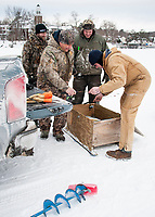 Dave Enser and Chet Wiess unload their fishing gear with Matt Adamchick and Robert Brehm on Meredith Bay during last winter's Great Meredith Rotary Fishing Derby.  (Karen Bobotas/for the Laconia Daily Sun)