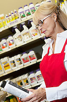 Senior woman looking at can in retail store