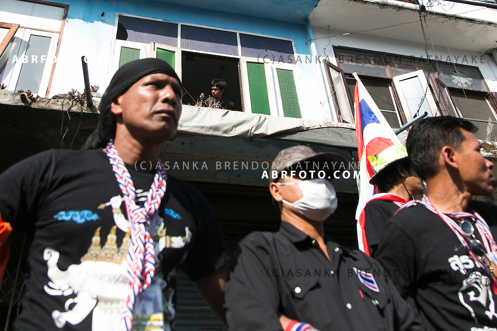 An Anti-Government protesters about to exit a window allegedly housing the suspect whom threw an explosive device injuring 30 people during an anti-government street rally on January 17, 2014 in Bangkok, Thailand