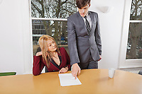 Young businesspeople reviewing documents at conference table