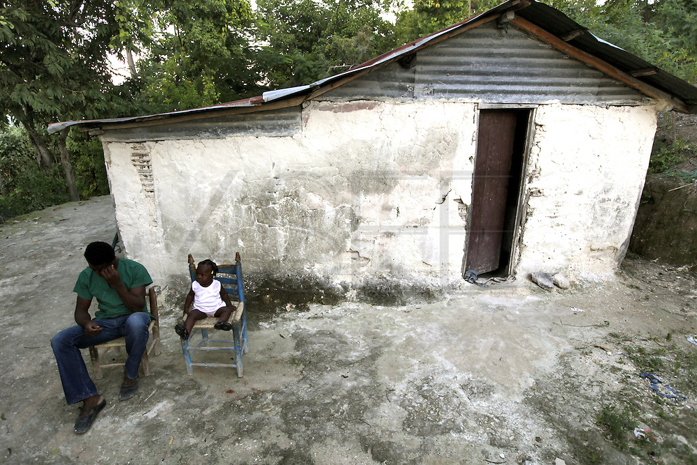 2009/11/16 20:20:55 / haiti 2009 / _MG_2402<br /> PHOTO PETER PEREIRA<br /> <br /> ++ Unemployed Franz Pierre Louis 24 sits in front of his home with daughter Kimberly Pierre Louis, 9 months, as the day slowly crawls by high above Carrefour, Haiti.