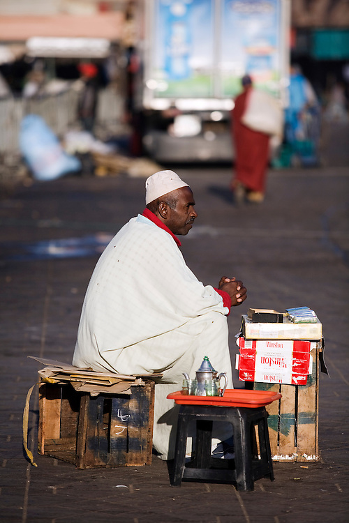 A vendor sits on his crate, selling  cigarettes as he waits for the morning traffic to begin in the main square of Djemaa el Fna in the city of Marrakech in Morocco.