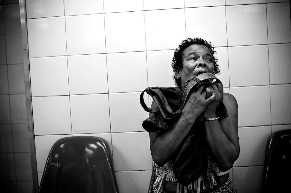 A woman cries and clasps the blood-stained blue jeans of her son while doctors work to stabilize him from four gun shot wounds to the chest at the trauma center at Perez Leon Hospital in the Petare slum in Caracas, Venezuela.