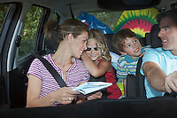 Family with two children (5-6) in car interior talking