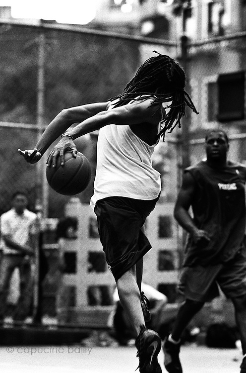 "June 10th 2003. New York, New York. United States..Located in the heart of Greenwich Village, the West 4th Street basketball Court, known as ""The Cage"", offers no seating but attracts the best players and a lot of spectators as soon as spring is around the corner..Half the size of a regular basketball court, it creates a fast, high level of play. The more people watch, the more intense the games get. « The Cage » is a free show. Amazing actions, insults and fights sometimes, create tensions among and inside the teams. The strongest impose their rules. Charisma is present..""The Cage"" is a microcosm. It's a meeting point for the African American street culture of New York. Often originally from Jamaica or other islands of the Caribbean, they hang out, talk, joke, laugh, comment the game, smoke… Whether they play or not, they're here, inside ""The Cage"". Everybody knows everybody, they all greet each other, they shake hands and hug: ""Yo, whasup man?"""