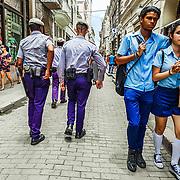 A young couple walks past authorities in Havana, Cuba