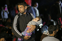 © London News Pictures. A migrant holds his child during a stand off with police close to the Hungarian and Serbian border town of Roszke, Hungary, September 8 2015. The UN's humanitarian agencies are on the verge of bankruptcy and unable to meet the basic needs of millions of people because of the size of the refugee crisis in the Middle East, Africa and Europe, senior figures within the UN have told the media.   Picture by Paul Hackett /LNP