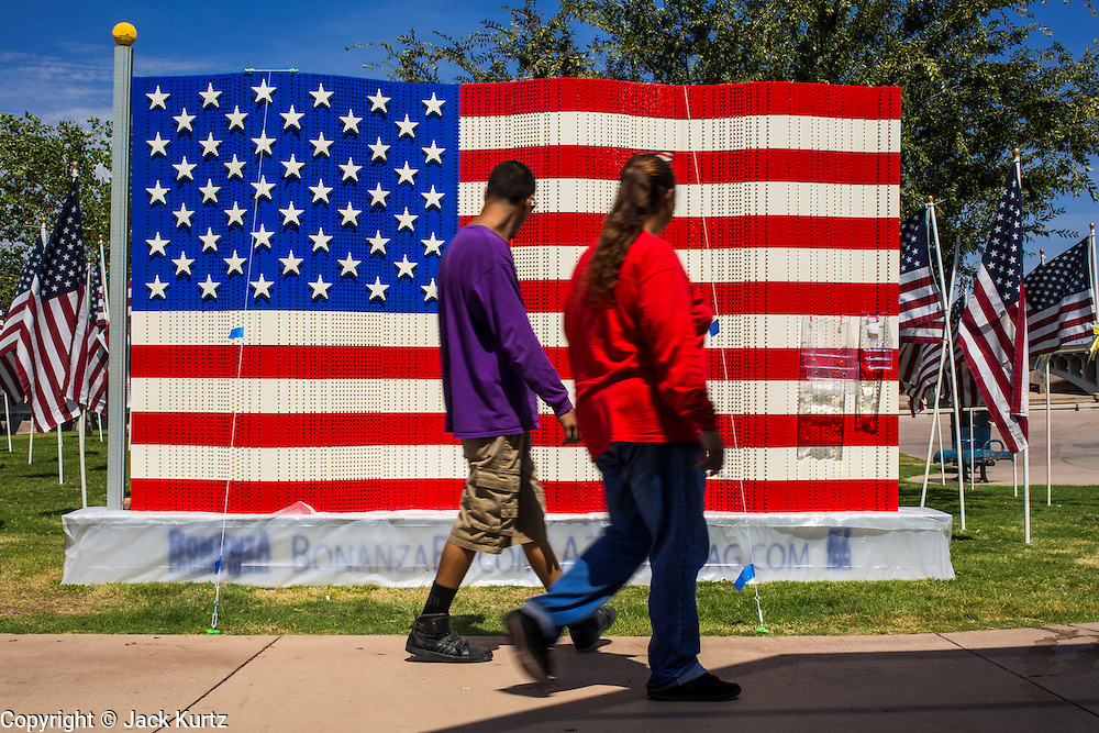 10 SEPTEMBER 2012 - TEMPE, AZ:      People walk past a large American flag made of Legos at the Healing Field in Tempe, AZ, Monday. The Exchange Club of Tempe and the city of Tempe are hosting the 9th Annual Healing Field display. The annual event posts three thousand American flags in the Tempe Beach Park. The flags are 3?X5?  and stand 8? tall. The display is a tribute to those who died in the terrorist attacks of September 11, 2001. Nearly 3,000 people were killed when terrorists affiliated Al-Qaeda crashed commercial airliners into the World Trade Center in New York, the Pentagon in Arlington, VA, and a field in Ohio.   PHOTO BY JACK KURTZ
