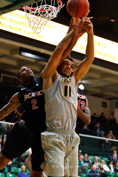 Dec 10, 2011; San Francisco CA, USA;  San Francisco Dons center Justin Raffington (11) fights Pacific Tigers guard Colin Beatty (2) for a rebound during the first half at War Memorial Gym.  Mandatory Credit: Jason O. Watson-US PRESSWIRE