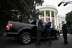 """WASHINGTON, DC - JULY 23: U.S. President Donald Trump (L) talks to Ford Motor Company Vice President of U.S. Government Relations Curt Magleby (2nd L) in front of an F-150 pick up truck during the 2018 Made in America Product Showcase July 23, 2018 at the White House in Washington, DC. The White House held the showcase to """"celebrates every state's effort and commitment to American-made products, and will allow these companies to speak with senior Administration officials, including the President, the Vice President, members of the Cabinet, and senior staff."""" (Photo by Alex Wong/Getty Images)"""