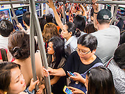 "22 MAY 2014 - BANGKOK, THAILAND: Thais crowd onto the BTS Skytrain after work to get home before a curfew goes into effect. The Thai army suspended civilian rule, suspended the constitution and declared the ""military takeover of the nation."" The announcement came just before evening as a meeting between civilian politicians and the army was breaking up with no progress towards resolving the country's political impasse. Civilian politicians were arrested when the meeting ended. The army also declared a curfew from 10PM until 5AM.    PHOTO BY JACK KURTZ"