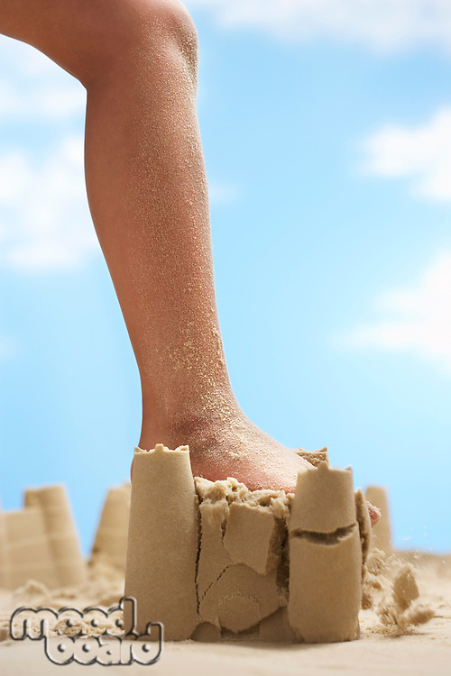Child stepping on sand castle low section