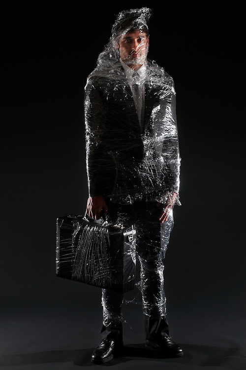 Businessman wrapped in plastic wrap - illustration of Corporate Transparency (Model is D.Mciver)
