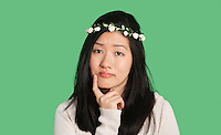 Portrait of a beautiful young woman thinking with hand on her chin over green background