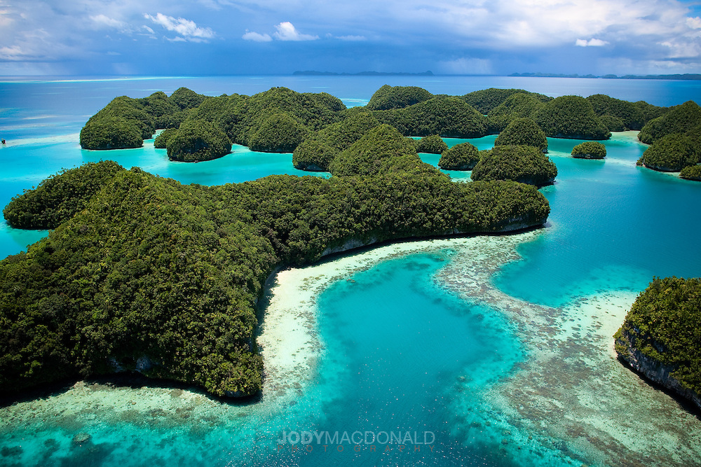 "The amazing colors of the protected ""70 islands"" in the surreal archipelago of Palau can only be seen, and appreciated from the sky.  Protected for nearly 50 years this small group of kaleidoscopic motus hosts a wide range of sea life, including the endangered dugong, or sea cow."