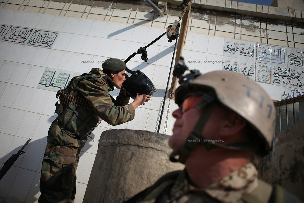 A german soldier watches an afghan comrade drinking water from a well. Joint patrol of german Bundeswehr and Afghan National Army in and around Nawabad. By rising presence ISAF wants to push out remain Taliban and occupy the former insurgent held region of Chahar Darah. Soldiers talk to local, recruit informers, check cars and try to figure out essential needs of Nawabads local polupaltion. late October 2011 Kunduz based 3.Task Force started a several days operation in and around Nawabad (District Chahar Darah), west of Kunduz, northern Afghanistan. During the Operation Orpheus about 100 german infantery soldiers rolled out for patrols through the town and surrounding areas, which were expected as a retreat zone of insurgents.
