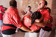 men carry a girl who has fallen when he has raised a human tower.Colla Vella Xiquets de Valls.'Castellers' building human tower, a Catalan tradition.Biannual contest. bullring.Tarragona, catalonia,Spain