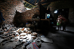 A pair of sisters watch tv in their partly collapsed house in Pariaman, West Sumatra, Indonesia after a powerful earthquake rocked western Indonesia 04 October 2009. The West Sumatra disaster management coordination unit put the death toll from Wednesday's earthquake in Padang and its neighboring town Pariaman at 448, with over 2,000 others injured.