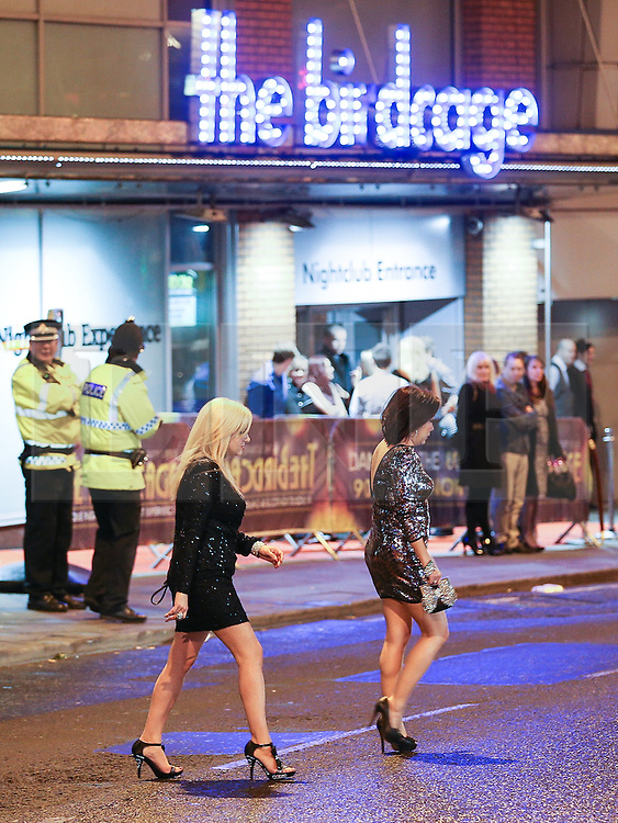 © Licensed to London News Pictures . 01/01/2014 . Manchester , UK . Two women cross the road outside the Birdcage nightclub as police look on . Revellers see in the New Year in Manchester today (January 1st 2014) as police report that officers are at full stretch responding to calls . Photo credit : Joel Goodman/LNP