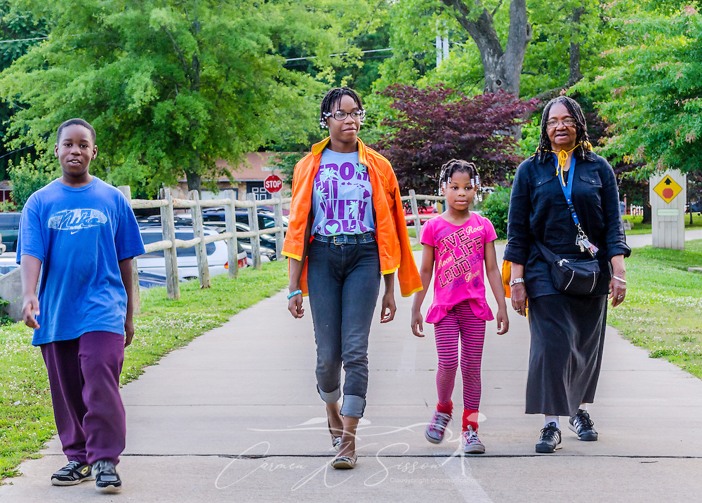 From left, siblings Darnell Middlebrooks, Danielle Middlebrooks, and Danolia Middlebrooks, walk with their grandmother, Magnolia White, June 2, 2014, at Stone Mountain Village in Stone Mountain, Georgia. (Photo by Carmen K. Sisson/Cloiudybright)