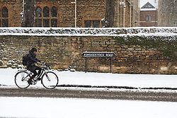 © Licensed to London News Pictures.  18/01/2013. OXFORD, UK. A student cycles through central Oxford during heavy snow. The Met Office has issued an amber warning for heavy snow for a large part of England. Photo credit :  Cliff Hide/LNP