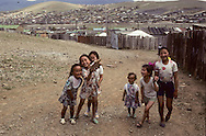 Mongolia. Ulaanbaatar. An area of traditional  - ger -  tents in Ulan Bator.  / The capital is located in a Valley of the Kenti mountains.  A couple returns to their home in a suburb, one of the  - ger -  zones marked off by high wooden fences.  In the background we can see the town centre with its official buildings and concrete apartment buildings (northwest Ulan Bator).    / Enfants des quartiers pauvres de Oulan Bator.   / 108      /  P0002224