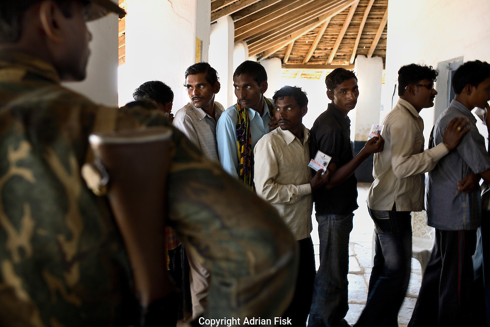 Under armed security from the police locals cast their vote at a polling station in Raipur district in the centre of Chhattisgarh. Naxalites oppose the democratic process believing in a one party communist state and as a result have routinely attacked polling stations.