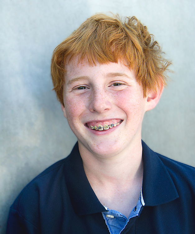 Redhead boy with braces and freckles, 12 years old, looking at camera with big smile