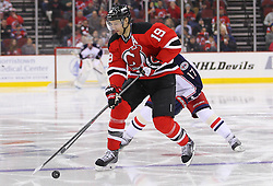 Feb 27, 2014; Newark, NJ, USA; New Jersey Devils center Travis Zajac (19) skates with the puck while being defended by Columbus Blue Jackets center Brandon Dubinsky (17) during the second period at Prudential Center.