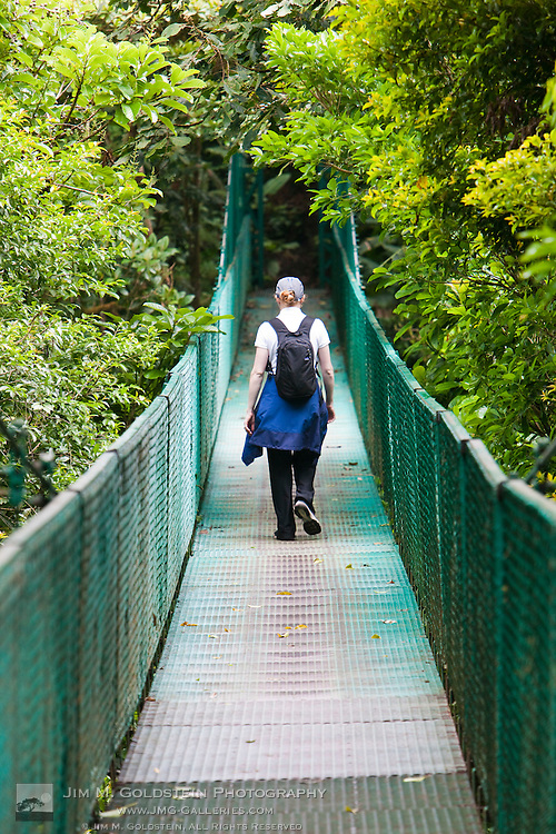 A young woman walks above the Costa Rica Cloud Forest canopy on a walking bridge in the Monteverde Cloud Forest Reserve in Selvatura Adventure Park, Costa Rica