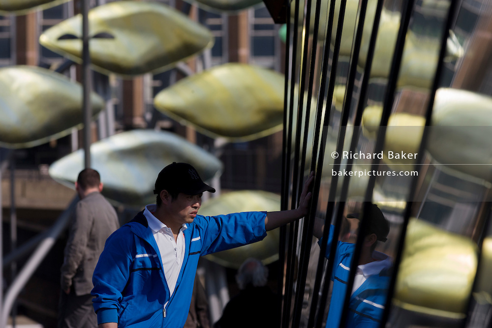 Young man of Chinese descent deep in thought on walkway with the new Olympic kinetic artwork called the Shoal at Stratford. 'The Shoal' at the Stratford Centre, east London, is made up of around 100 titanium clad 'leaves' mounted between 15 and 19 metres high on metal posts. Worth £13.5m, the Shoal is part of The Stratford Town Centre Public Realm Project, designed and manufacturered using 3D technology.