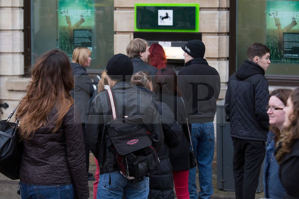 """© Licensed to London News Pictures. 7/12/2013. Lincoln, UK. Lincoln City Centre was packed with Christmas shoppers this weekend. Pictured, one of the many queues at a cash machine in the centre of Lincoln. Thousands of shoppers filled the City Centre and stewards were called in to direct people up the narrow """"Steep Hill"""" towards the upper area of Lincoln near the Cathedral. Photo credit : Dave Warren/LNP"""