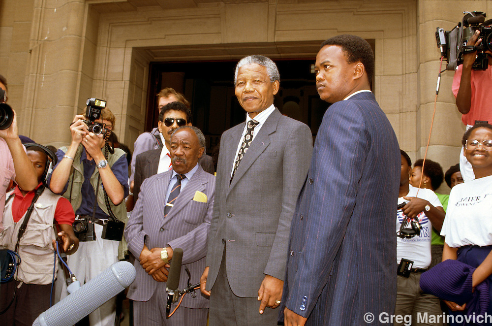 Nelson Mandela, ANC leader with Alfred Nzo and bodyguards outside the Johannesburg High Court. South Africa. 1991-1993.