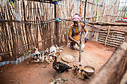 VSO ICS volunteer Francisca Mlingwa feeding the family chickens in her host home. Volunteers stay with local families get the full experience. Lindi, Lindi region. Tanzania.