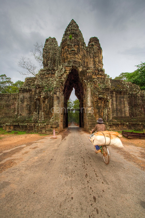 Bicyclist carries goods through gate at Angkor Wat, Cambodia