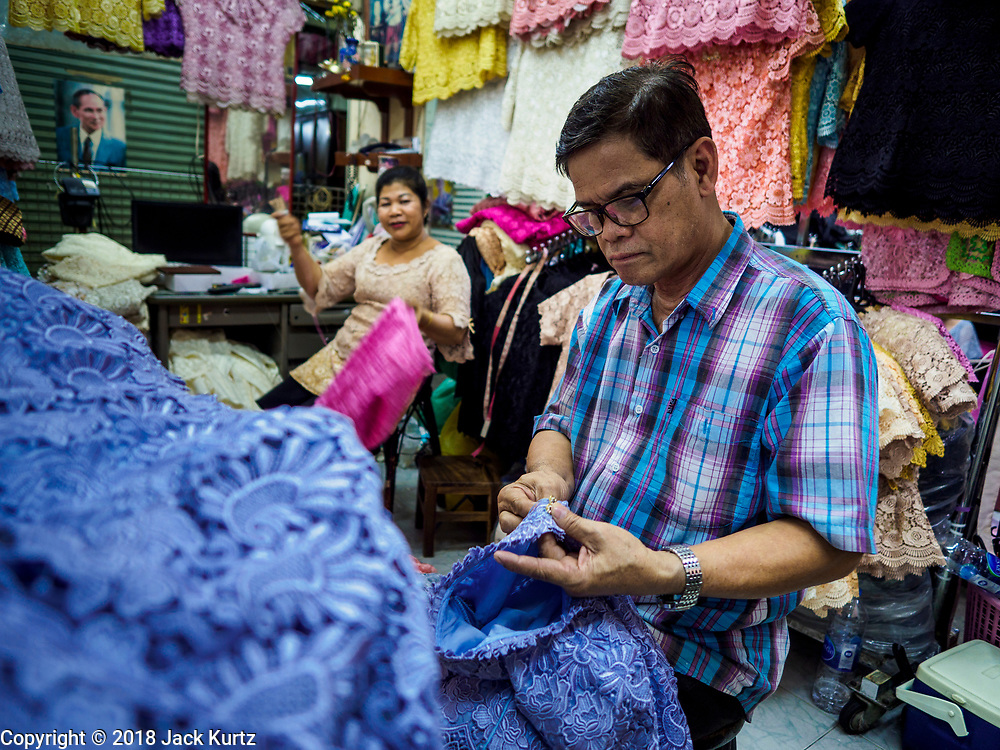 23 FEBRUARY 2018 - BANGKOK, THAILAND: A couple puts the finishing touches on clothes they sew in their shop in Pratunam Market. Pratunam Market was one of the largest clothing markets in Bangkok. New airconditioned markets, like Platinum and Palladium malls opened nearby, siphoning away customers. Now there are only a handful of merchants left in the market and Bangkok city officials have plans to shut the market and redevelop the land.    PHOTO BY JACK KURTZ