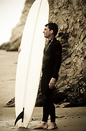 A surfer in a wetsuit holding his surfboard, standing on the beach with cliffs in the background looking out onto the ocean in Santa Barbara, California.  (releasecode: jk_mr1025) (Model Released)